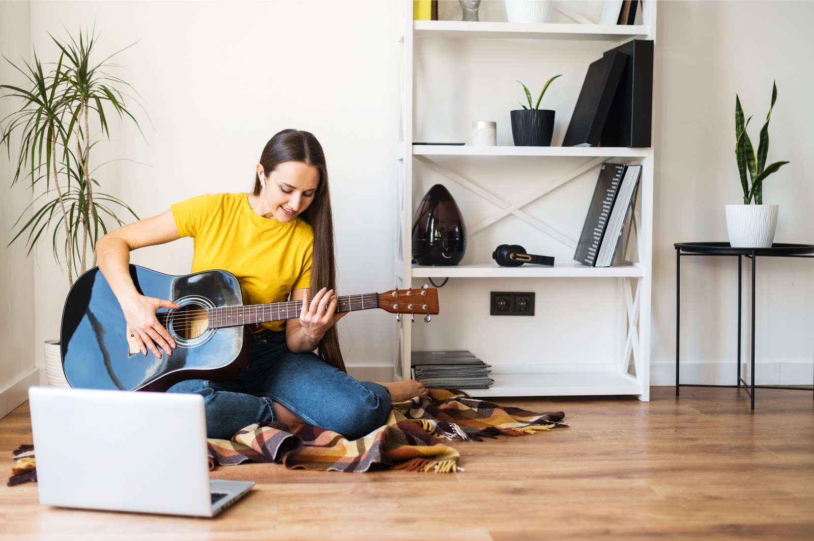 Person learning the guitar as a hobby to help with addiction recovery