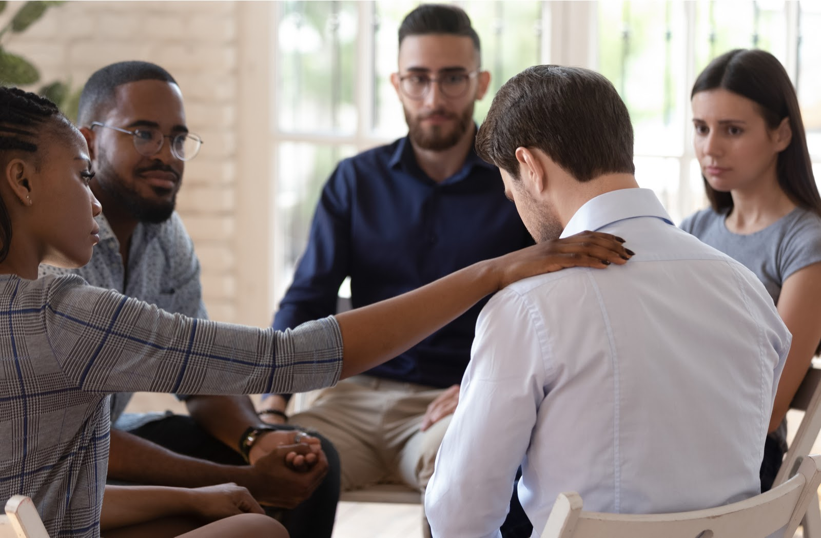 Circle of supportive men and women in addiction treatment program