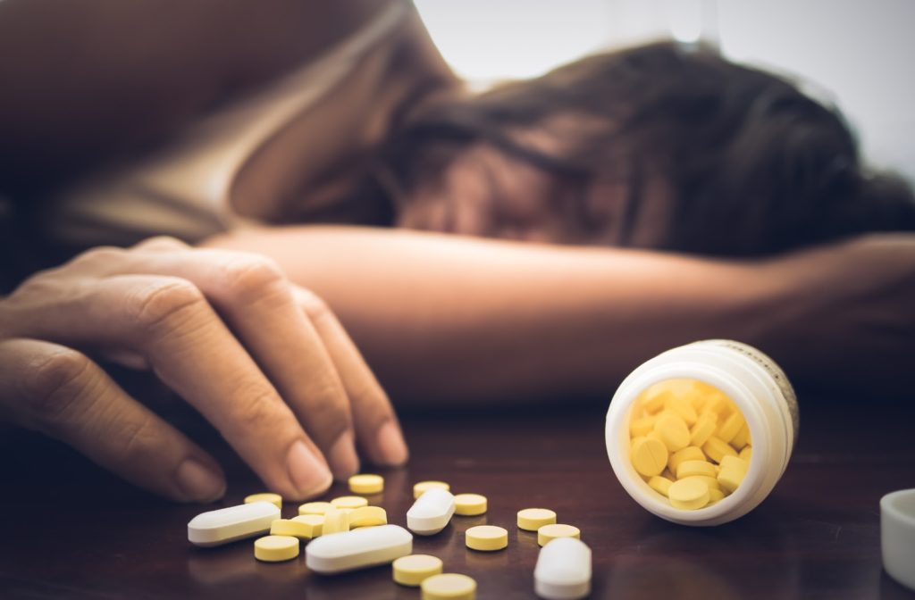 Unconscious woman lying on table next to open pill bottle