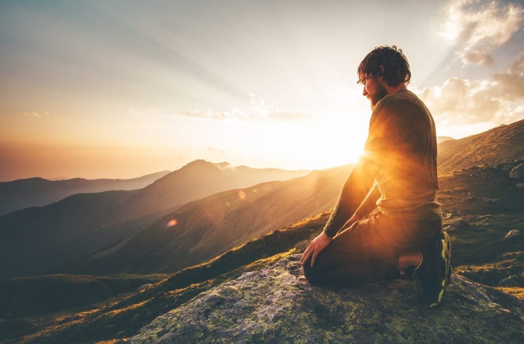 A man engages in mindfulness and prayer at sunset on a beautiful mountaintop