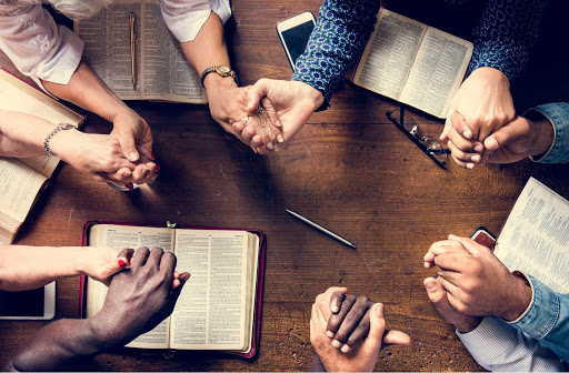 A group of people hold hands in prayer during bible study as part of addiction recovery