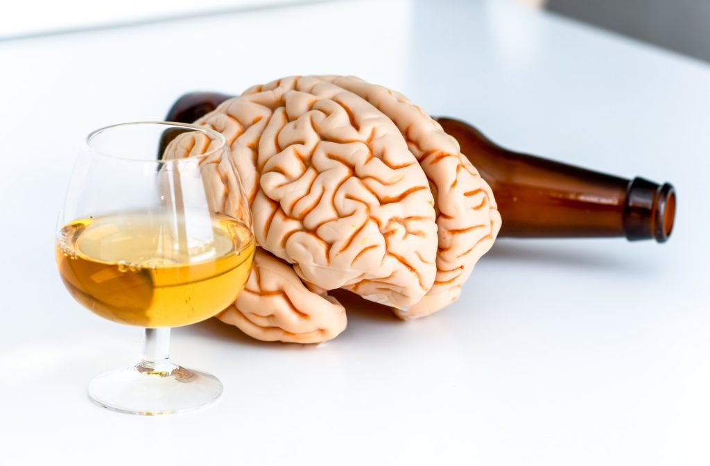 Human brain alongside a beer bottle and glass of alcohol.
